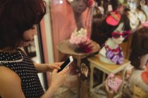 Mulher elegante usando seu telefone celular ao fazer compras de janela — Fotografia de Stock