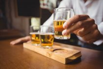 Close-up of bartender holding whisky shot glass at bar counter in bar — Stock Photo