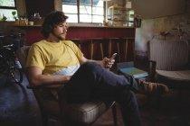 Механическое прослушивание музыки на мобильном телефоне в мастерской — стоковое фото