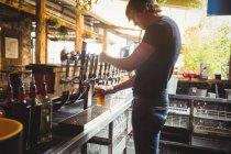 Бар тендер заповнення пива з бар насосу в барна стійка — стокове фото