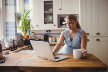Mulher grávida usando laptop enquanto toma café na cozinha em casa — Fotografia de Stock