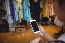 Hand der Frau mit Handy in Bekleidungsgeschäft — Stockfoto