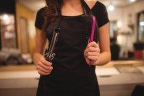 Meados de seção de cabeleireiro feminino segurando máquina de encrespador de cabelo e escova de cabelo no salão — Fotografia de Stock