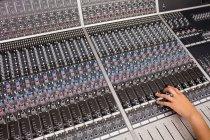 Mão de uma estudante usando misturador de som em um estúdio — Fotografia de Stock