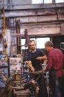 Стеклодувы, формирующие стекло на трубе стеклодувного завода — стоковое фото