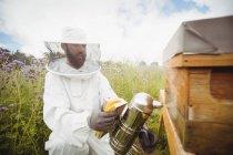 Imker setzt Bienenraucher auf Feld ein — Stockfoto