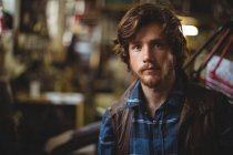 Retrato mecánico guapo en taller - foto de stock