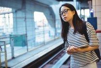 Giovane donna in attesa di treno alla stazione ferroviaria — Foto stock