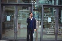 Empresario hablando por teléfono móvil fuera de oficina - foto de stock