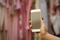 Рука женщины, держащей мобильный телефон в бутике — стоковое фото
