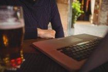 Sección media del hombre con el ordenador portátil en el bar - foto de stock