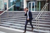 Бизнесмен разговаривает по мобильному телефону, когда идет по лестнице — стоковое фото
