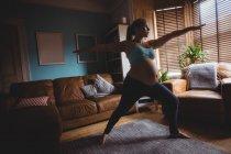 Беременная женщина, выполняющая упражнения на растяжку в гостиной дома — стоковое фото
