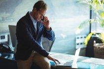 Hombre de negocios hablando en el teléfono móvil mientras usa el ordenador portátil en la oficina - foto de stock