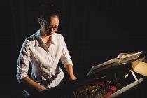 Красивая женщина играет на пианино в музыкальной студии — стоковое фото