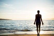 Задний вид женщины, практикующей йогу на пляже в солнечный день — стоковое фото
