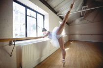Side view of Ballerina stretching at barre in studio — Stock Photo