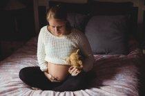 Беременная женщина держит плюшевого мишку в спальне дома — стоковое фото