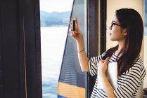 Красивая женщина фотографирует на мобильный телефон с корабля — стоковое фото