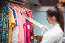 Вибір одягу на вішалці в магазині одягу жінка — стокове фото