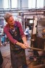 Стеклодувка нагревательного стекла в печи на стекольном заводе — стоковое фото