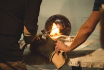 Team of glassblowers blowing propane gas flame on finished piece of glass at glassblowing factory — Stock Photo