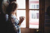 Женщина смотрит в окно, когда пьет кофе дома — стоковое фото