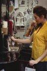 Жінка, дивлячись на марочні jar у антикварні магазин — стокове фото