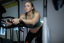 Pregnant woman working out on exercise bike at gym — Stock Photo