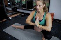 Беременная женщина, занимающаяся йогой в спортзале — стоковое фото