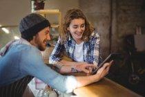 Механик и официант с помощью цифрового планшета на стойке в мастерской — стоковое фото