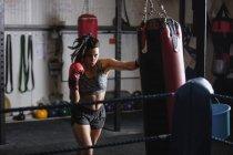 Уверенная женщина боксер практикующая бокс с боксерской грушей в фитнес-студии — стоковое фото