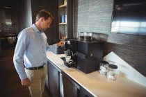 Businessman preparing coffee in coffee maker at cafeteria — Stock Photo