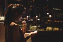 Jovem mulher usando telefone celular enquanto se gelado à noite — Fotografia de Stock