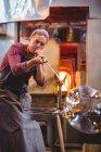Стеклодувка, формирующая стекло на трубе стеклодувного завода — стоковое фото