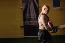 Вид сбоку на мускулистого тайского боксера, занимающегося боксом в тренажерном зале — стоковое фото