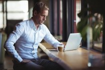 Uomo d'affari fiducioso che lavora su laptop con un caffè sul tavolo — Foto stock