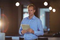 Retrato de un hombre de negocios usando tableta digital en la oficina - foto de stock