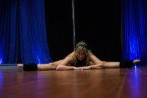 Hermosa bailarina de polo practicando piernas divididas y mirando a la cámara - foto de stock