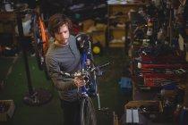 Механик с велосипедом в велосипедной мастерской — стоковое фото