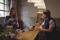 Serveuse préparant le café au comptoir tout en mécanicien utilisant un ordinateur portable en atelier — Photo de stock