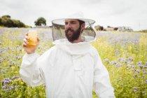 Apicultor segurando garrafa de mel no campo — Fotografia de Stock