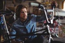 Mechanic examining bicycle in workshop — Stock Photo