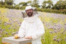 Imker hält Flasche Honig auf Bienenstock im Feld — Stockfoto