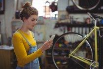 Механік за допомогою мобільного телефону в магазин велосипедів — Stock Photo