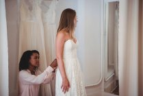 Woman trying on wedding dress in a studio with the assistance of fashion designer — Stock Photo