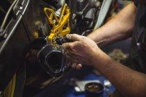 Primo piano del meccanico che esamina la moto in officina — Foto stock