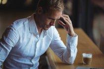 Uomo d'affari teso seduto in un caffè con una tazza di caffè — Foto stock