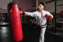 Людина, що практикують карате з боксерської груші в фітнес-студія — стокове фото
