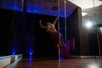 Bailarina de poste practicando pole dance en estudio - foto de stock